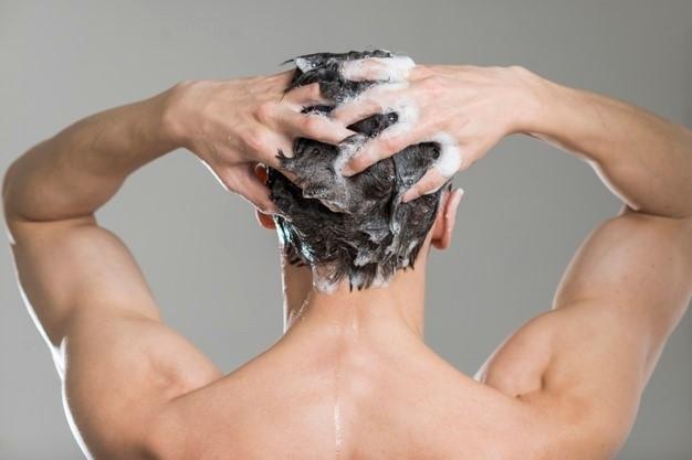 homem-lavando-o-cabelo-com-cosméticos-naturais